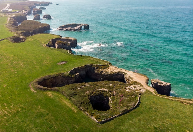 Luchtfoto kathedralen strand met groene velden en blauwe zee, galicië, lugo, spanje
