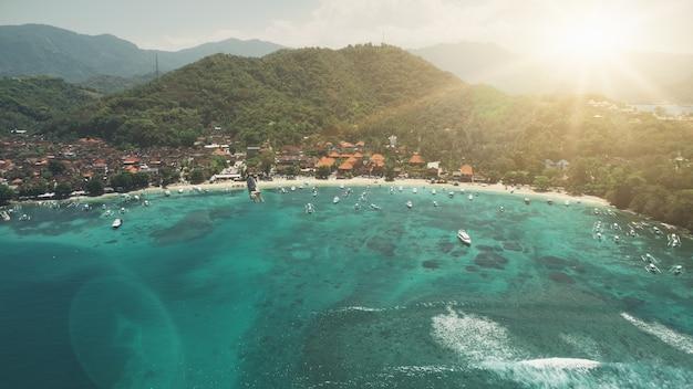 Luchtfoto kristal oceaan haven baai wit strand en groene bos bergen in zonsondergang zacht licht
