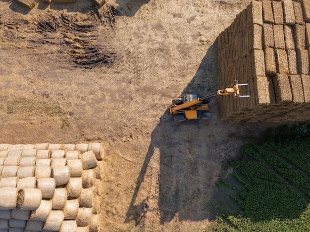 Luchtfoto landbouwmachines trekker stapelt balen hooi in het veld. foto van drone. herfst oogst. bovenaanzicht