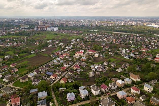 Luchtfoto landschap van kleine stad of dorp met rijen van residentiële huizen en groene bomen.