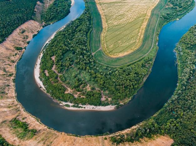Luchtfoto landschap van kronkelende rivier in groen veld