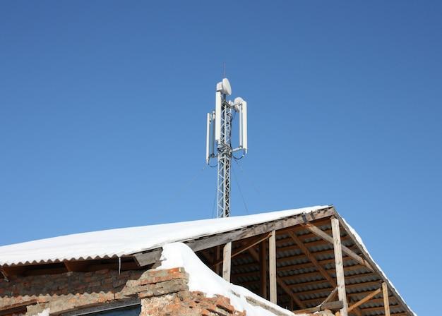 Luchtfoto mobiele communicatie op een dak van het oude huis tegen de blauwe hemel