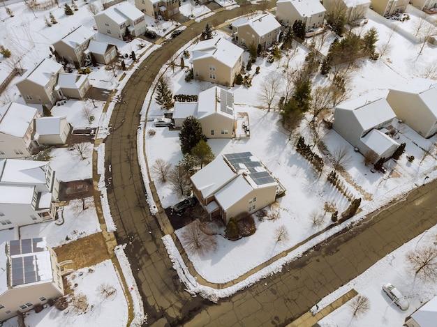 Luchtfoto naar beneden op overdekte huizen en wegen op binnenplaatsen in de winter met sneeuw bedekt met sneeuw
