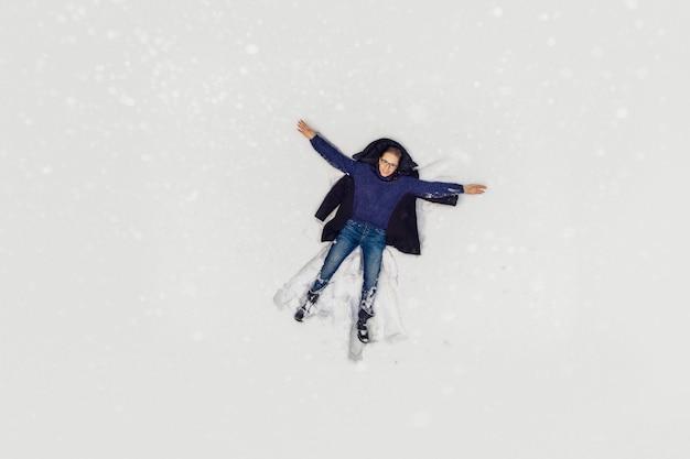 Luchtfoto naar vrouw liggend in de sneeuw