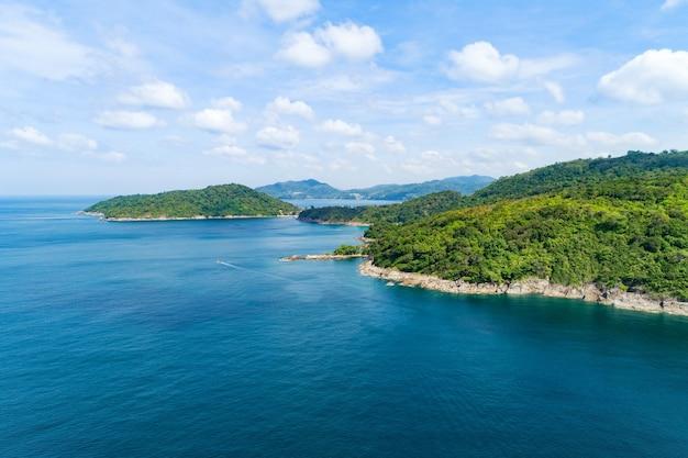 Luchtfoto op de kustlijn van de zee met stenen rotsen en bergen regenwoud. prachtig natuurlijk zeegezicht op de zomertijd. uitzicht op de westkust van het eiland phuket, thailand.