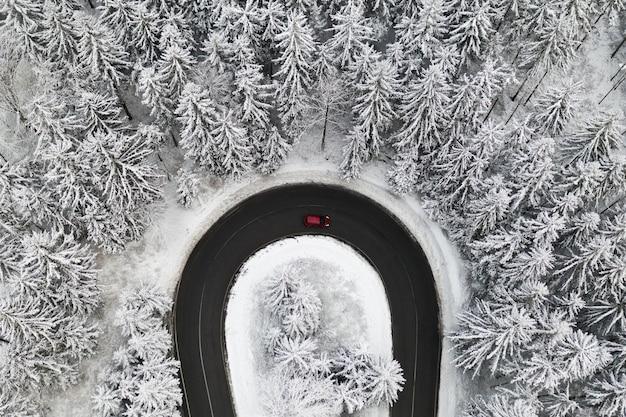 Luchtfoto op de weg in het bos met één auto in de winter. winterlandschap met hoge pijnbomen bedekt met sneeuw.
