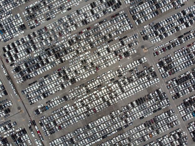 Luchtfoto over enorme buiten parkeerplaats met veel nieuwe voertuigen.
