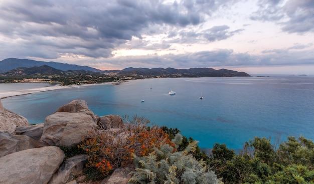 Luchtfoto panoramisch uitzicht op het strand en de zee met azuurblauwe turquoise kristalheldere water bergen op de achtergrond in villasimius sardinië sardegna eiland italië vakantie beste stranden in sardinië
