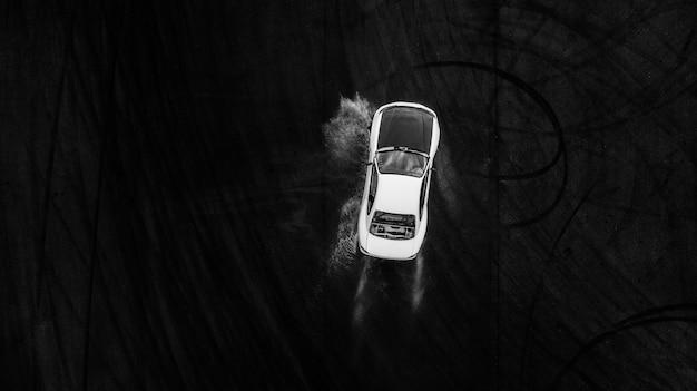 Luchtfoto professionele rijder afdrijvende auto op natte race circuit, met water splash.