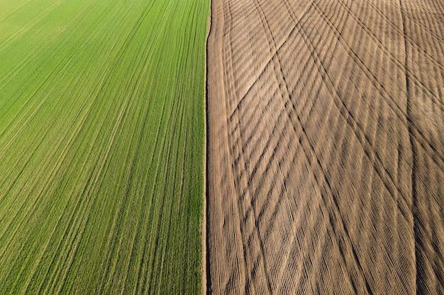 Luchtfoto rijen grond voor het planten van voren rijpatroon in een geploegd veld voorbereid voor het planten van gewassen in de lente landbouwpercelen van verschillende kleuren