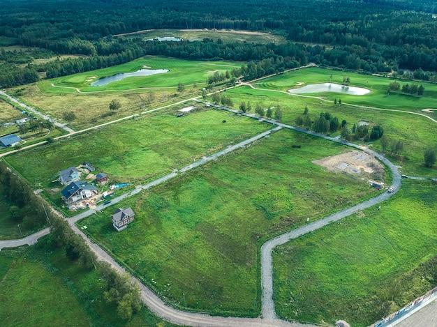 Luchtfoto's van golfclub, groene gazons, bossen, grasmaaiers