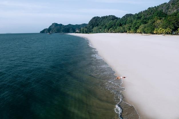 Luchtfoto: schattige vrouw in een wit zwempak liggend op de kust