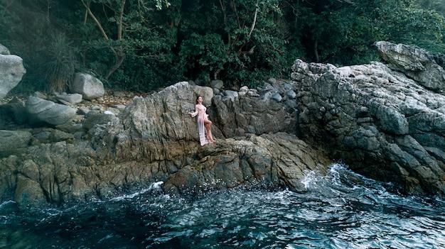 Luchtfoto: sexy foto van een mooie blonde poseren die in een halfnaakte witte jurk tussen de rotsen bij de kust met golven staat. drone foto.