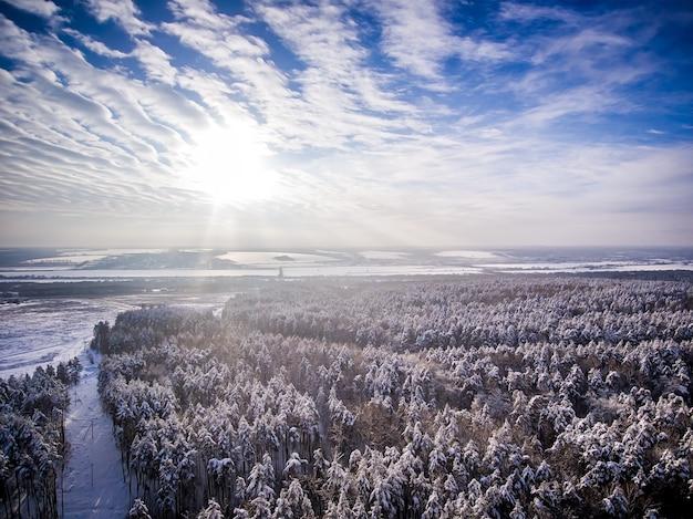 Luchtfoto sneeuw winter bosveld in de buurt van weg bevroren rivier wolken met zon in blauwe lucht