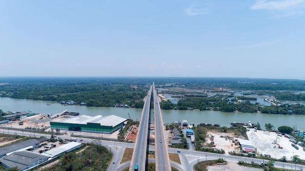 Luchtfoto snelweg verkeer weg met auto's. bekijk boven geweldige luchtfoto van de weg en de skyline. lange brug in surat thani, thailand.