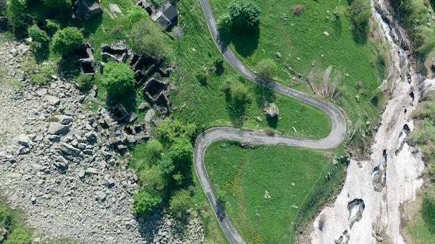 Luchtfoto: top-down view staartspin over kronkelende bergweg op de italiaanse alpen.