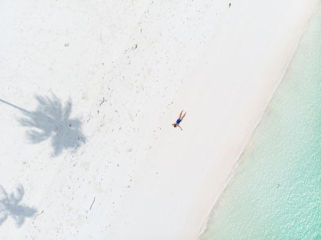 Luchtfoto top down weergave tropisch strand caribische zee. vrouw die tussen palmschaduw zonnebaadt op het witte turkooise water van het zandstrand
