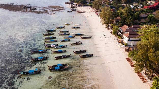 Luchtfoto uitzicht over groep van lange staart boten in zonsopgang strand. koh lipe-eiland, satun, thailand