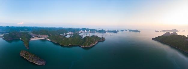 Luchtfoto unieke weergave vietnam cat ba baai met drijvende vissersboten op zee, cloudscape tropisch weer inspirerende zonsondergang, epische skyline van de stad en wolkenkrabber, schilderachtige groene berg.