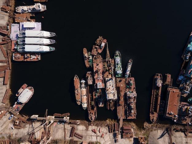 Luchtfoto van afgemeerde oude binnenschepen en schepen in de rivierhaven
