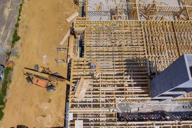Luchtfoto van appartement inlijsten van een nieuw huis in aanbouw met vorkheftruck stapelaar houten planken de bouwafvalcontainers