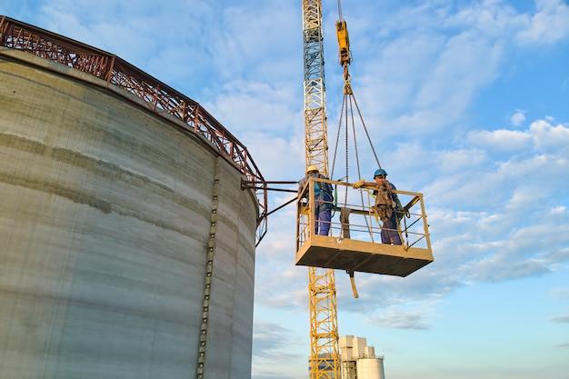 Luchtfoto van arbeiders op cementfabriek in aanbouw met hoge betonnen fabrieksstructuur en torenkranen op industrieel productiegebied.