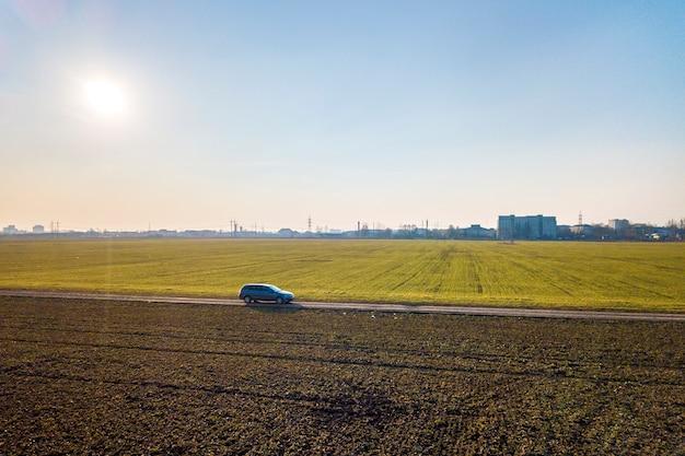 Luchtfoto van auto rijden door rechte grond weg door groene velden op zonnige blauwe hemel kopie ruimte achtergrond. drone fotografie.