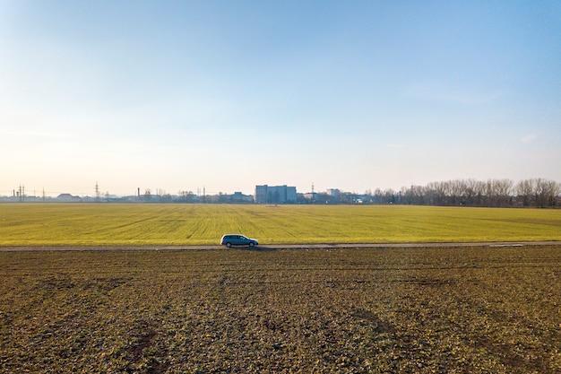 Luchtfoto van auto rijden door rechte grondweg door groene velden op zonnige blauwe hemel kopie ruimte achtergrond. drone fotografie.