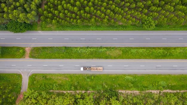 Luchtfoto van auto's en vrachtwagens op asfaltweg loopt door het groene bos