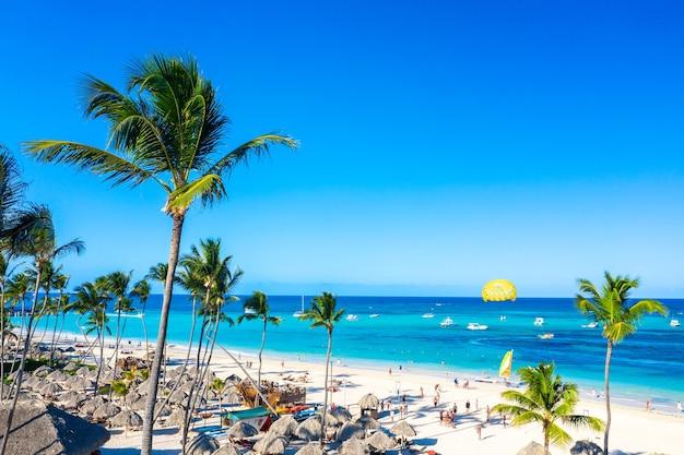Luchtfoto van bavaro strand punta cana tropische resort in dominicaanse republiek. prachtig atlantisch tropisch strand met palmen, parasols en parasailing-ballon.