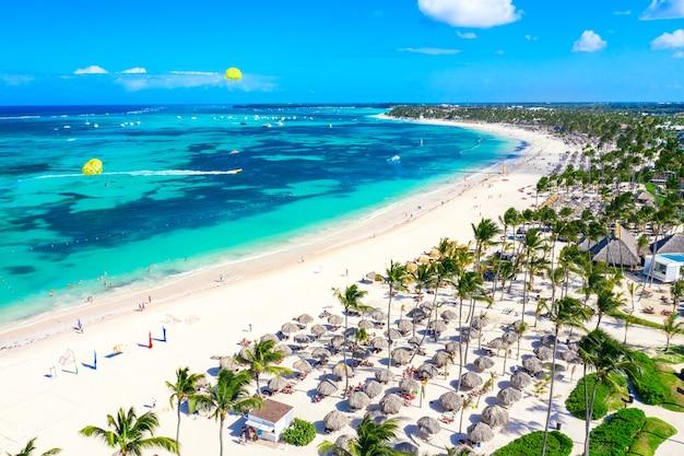Luchtfoto van bavaro strand punta cana tropische resort in dominicaanse republiek. prachtig atlantisch tropisch strand met palmen, parasols en parasailing ballonnen.