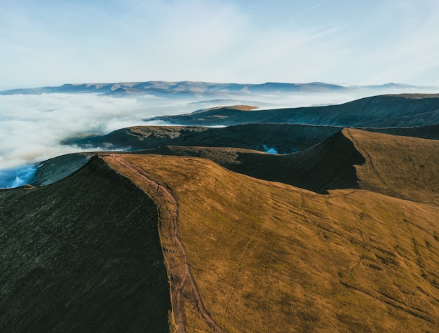Luchtfoto van bergen omringd met witte wolken