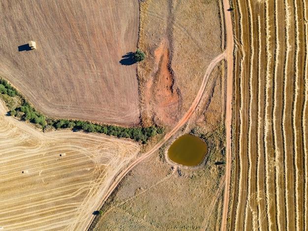 Luchtfoto van boerderij velden, onverharde wegen en waterbassin.