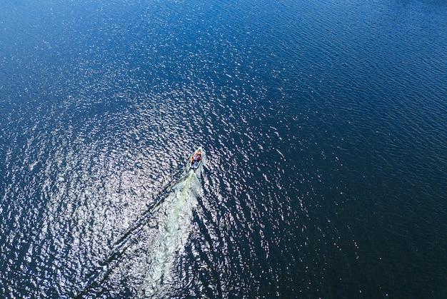 Luchtfoto van boot die drijft op zee of oceaan met blauw water tijdens de zomertijd, vakantie concept.
