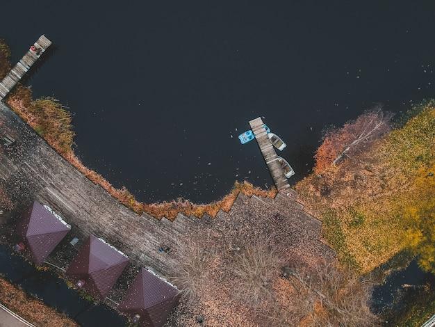 Luchtfoto van bos en blauw meer. saunahuis aan de oever van het meer. houten pier met vissersboten. st. petersburg, rusland.