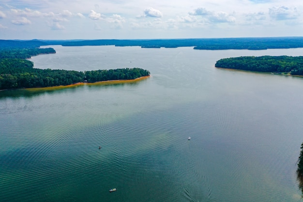 Luchtfoto van boten die over het meer met bomen en een bewolkte hemel reizen