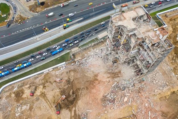Luchtfoto van bouwplaats met vernietigd industrieel gebouw en graafmachines en verkeersopstopping.