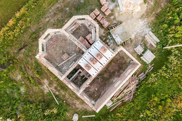 Luchtfoto van bouwterrein voor toekomstige woning, bakstenen kelderverdieping en stapels baksteen voor de bouw.