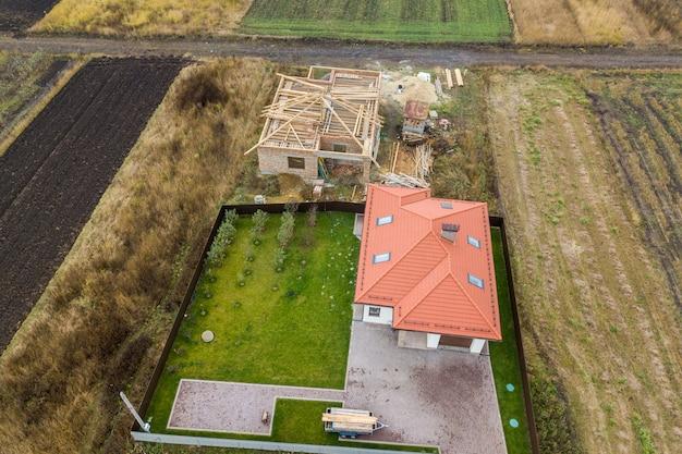 Luchtfoto van boven naar beneden van twee privéwoningen, een in aanbouw met houten dakframe en een andere afgewerkt met rood pannendak.