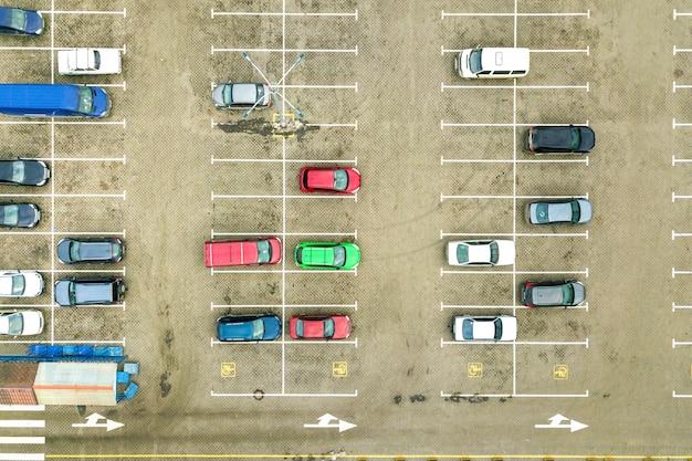 Luchtfoto van boven naar beneden van veel auto's op een parkeerplaats van een supermarkt of op een markt voor autodealers.