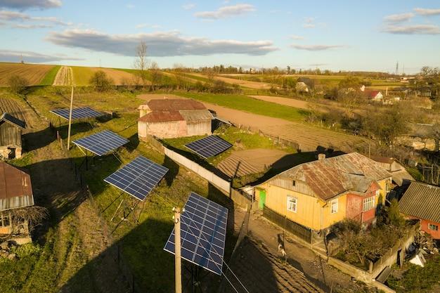 Luchtfoto van boven naar beneden van zonnepanelen in groene landelijke dorpswerf.