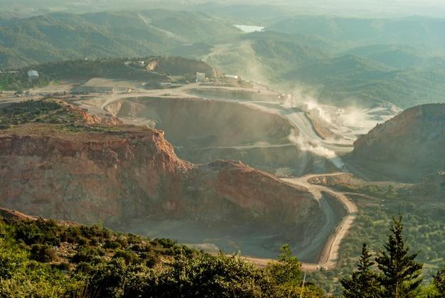 Luchtfoto van bovengrondse mijnbouwsteengroeve met veel machines aan het werk - weergave van bovenaf. steengroeve stenen, voor de bouw met blauwe lucht. mijnomgeving, industriële achtergrond. landelijk landschap,