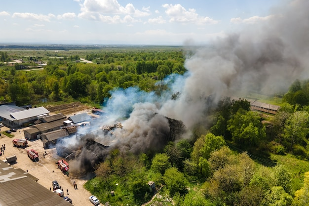 Luchtfoto van brandweerlieden die verwoest gebouw in brand blussen met ingestort dak en opstijgende donkere rook.