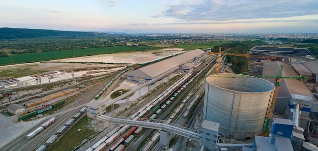 Luchtfoto van cementfabriek in aanbouw met hoge betonnen fabrieksstructuur en torenkranen op industrieel productiegebied. vervaardiging en wereldwijd industrieconcept.