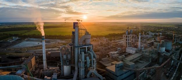Luchtfoto van cementfabriek met hoge betonnen fabrieksstructuur en torenkraan op industrieel productiegebied. vervaardiging en wereldwijd industrieconcept.