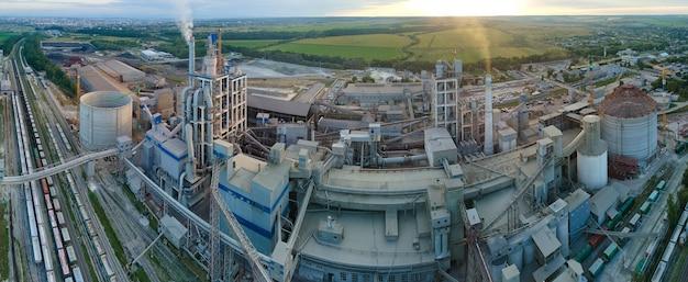 Luchtfoto van cementfabriek met hoge betonnen fabrieksstructuur en torenkraan op industriële productielocatie. vervaardiging en wereldwijd industrieconcept.