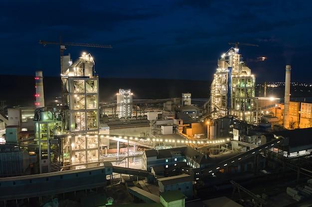 Luchtfoto van cementfabriek met hoge betonnen fabrieksstructuur en torenkranen op industrieel productiegebied 's nachts. vervaardiging en wereldwijd industrieconcept.