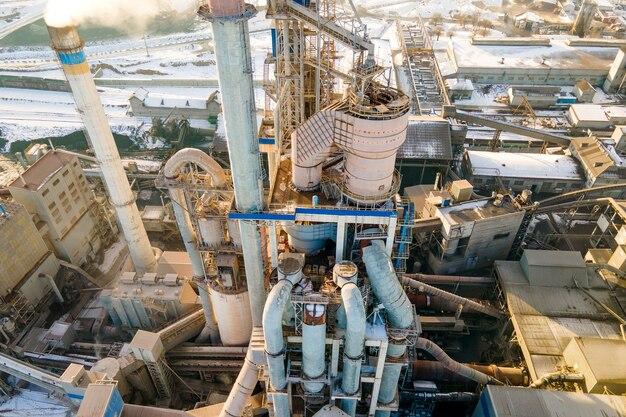 Luchtfoto van cementfabriek met hoge fabrieksstructuur en torenkraan op industrieel productiegebied bij zonsondergang.