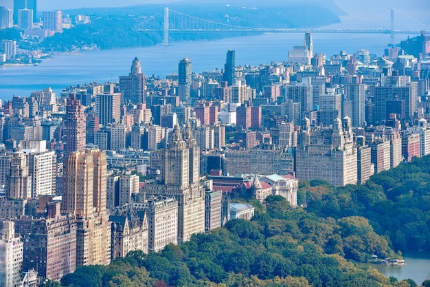 Luchtfoto van central park en rij gebouwen aan de upper west side. hudson river en george washington bridge op de achtergrond. manhattan, new york, verenigde staten.