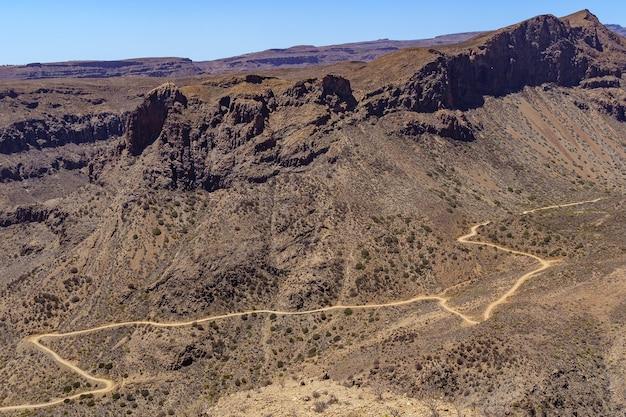 Luchtfoto van de bergen van gran canaria met een weg die rond de heuvel loopt en bochten maakt. spanje. europa.